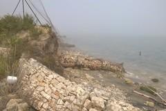 Argine costruito in zona Pai, pietre e terra corrose dal mare.